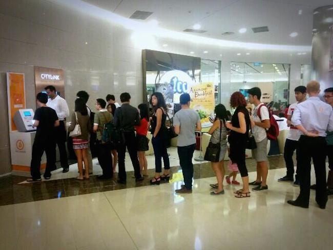 Orang dari Singapura menunggu di hadapan ATM Bitcoin